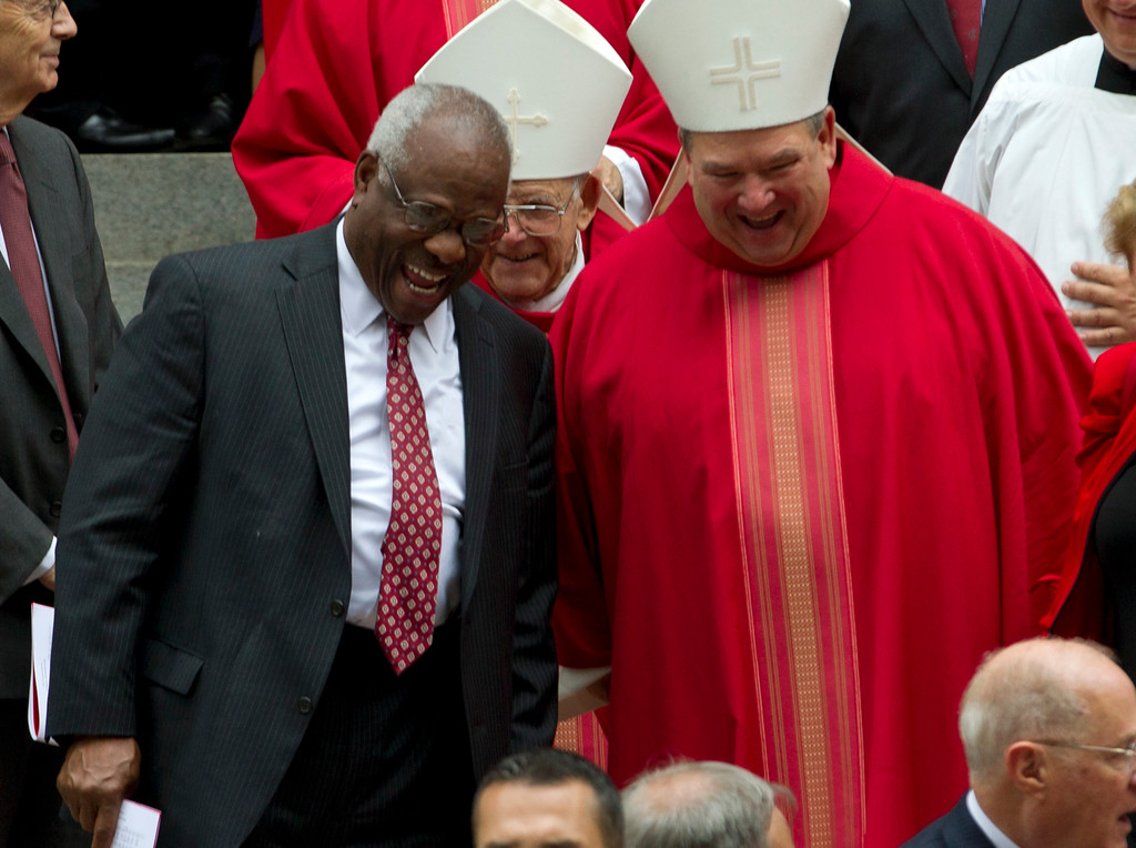 . U.S. Supreme Court Justice Clarence Thomas speaks with a member of the clergy as they leave St. Mathews Cathedral after the Red Mass in Washington on Sunday, Oct. 2, 2016. The Supreme Court\'s new term starts Monday, Oct. 3. (AP Photo/Jose Luis Magana)
