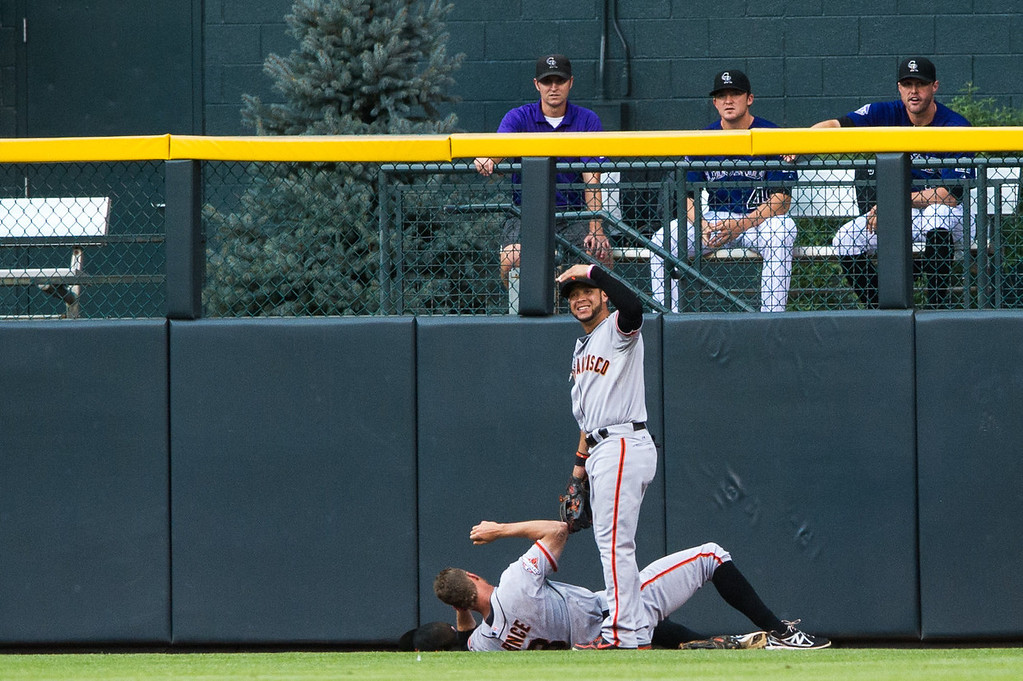 . Gregor Blanco #7 of the San Francisco Giants calls for help as Hunter Pence #8 lies on the ground in pain after running into the right field wall during the first inning of a game at Coors Field on August 26, 2013 in Denver, Colorado. Pence remained in the game for the remainder of the first inning. (Photo by Dustin Bradford/Getty Images)