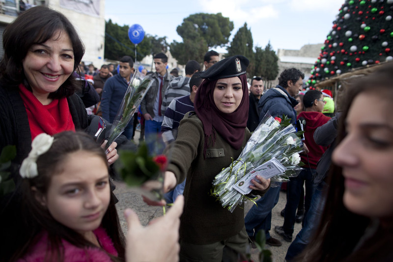 . A Palestinian policewoman gives out flowers outside the Church of the Nativity on December 24, 2014 in Bethlehem, West Bank. Every Christmas pilgrims travel to the church where a gold star embedded in the floor marks the spot where Jesus was believed to have been born.  (Photo by Lior Mizrahi/Getty Images)