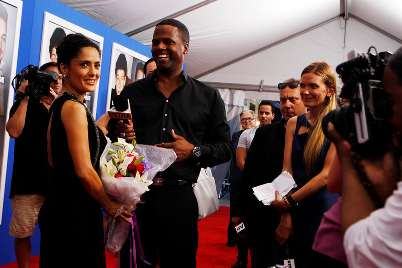 """. Cast member Salma Hayek smiles after being given flowers by television host AJ Calloway as she arrives for the premiere of the film \""""Grown Ups 2\"""" in New York, July 10, 2013. REUTERS/Lucas Jackson"""