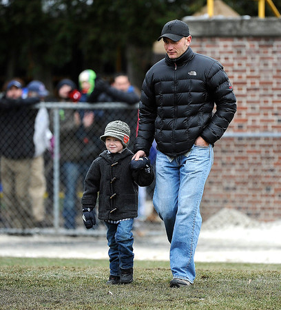 11/29/2014 Mike Orazzi | Staff Hometown hero Joseph Kapacziewski with his son Wyatt while being honored before the Battle for The Bell at Muzzy Field on Saturday.