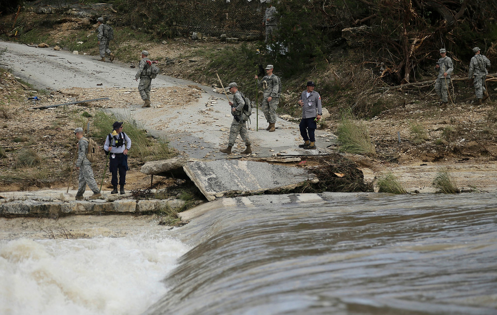 . Members of the National Guard and a search and rescue team work along the Blanco River, Tuesday, May 26, 2015, in Wimberley, Texas. Authorities say recovery teams continue to search for as many as a dozen missing people in an area where punishing rains have destroyed or damaged more than 1,000 homes and killed at least three people statewide this past weekend. (AP Photo/Eric Gay)