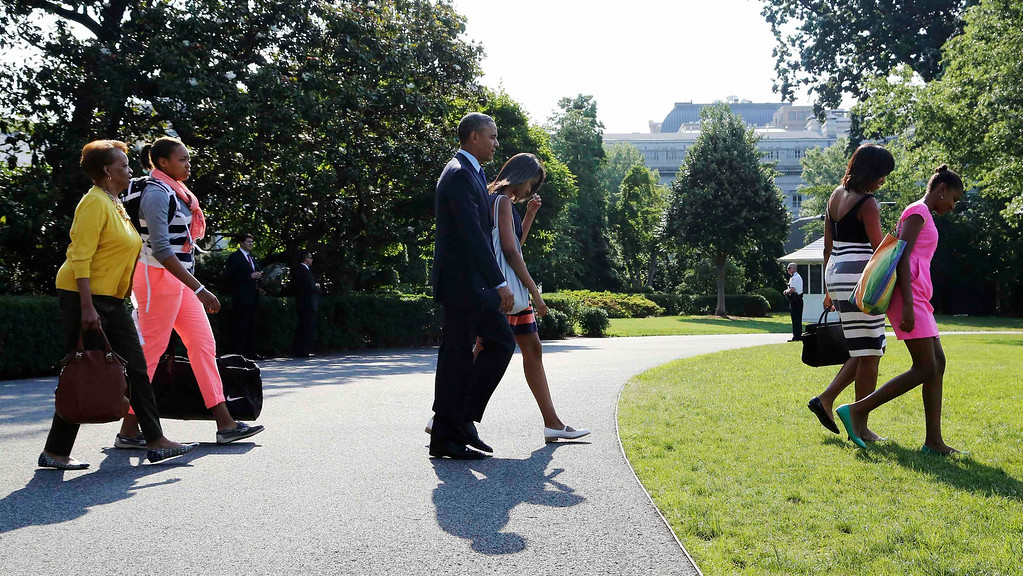 . U.S. President Barack Obama (C) and his family walk to the helicopter to depart for travel to Africa from the South Lawn of the White House in Washington, June 26, 2013. Obama\'s weeklong trip to Senegal, Tanzania and South Africa risks being overshadowed by the deteriorating health of South Africa\'s national hero and revered former leader, Nelson Mandela. Also pictured are Obama\'s mother-in-law Marian Robinson (L-R), his niece Leslie Robinson, his daughter Malia, first lady Michelle Obama and daughter Sasha.  REUTERS/Jonathan Ernst
