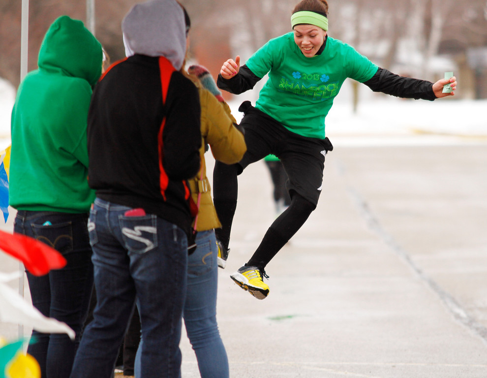 . Maria Stephans of Hartford, Wis. click her heels together as she crosses the finish line during the Shamrock Shuffle 5K Race/Walk in Hartford on Saturday, March 16, 2013. Proceeds from the race benefited the Hartford Union Varsity Club.  (AP Photo/The Daily News, John Ehlke)