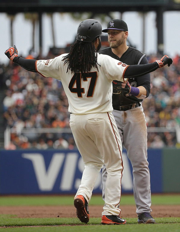 . San Francisco Giants\' Johnny Cueto (47) is tagged out by Colorado Rockies first baseman Mark Reynolds during the sixth inning of a baseball game in San Francisco, Saturday, May 7, 2016. (AP Photo/Jeff Chiu)