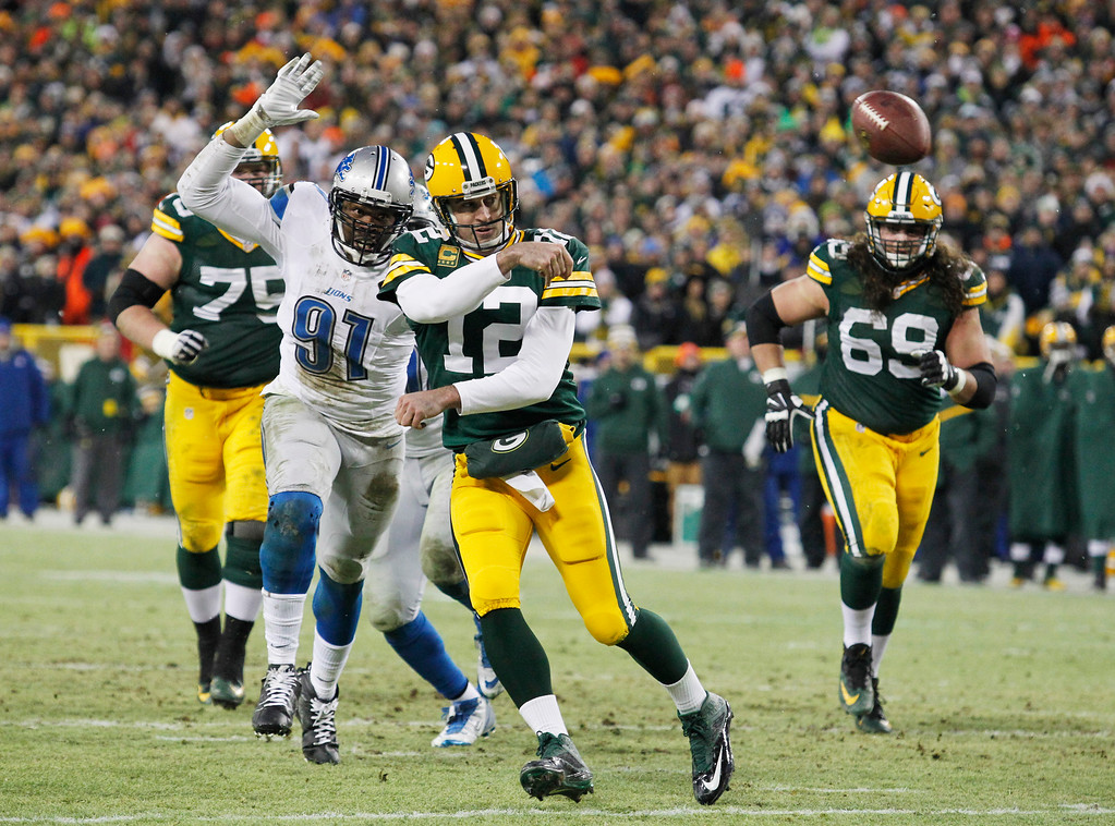 . Green Bay Packers\' Aaron Rodgers throws a touchdown pass to Randall Cobb during the first half of an NFL football game against the Detroit Lions Sunday, Dec. 28, 2014, in Green Bay, Wis. Rodgers injured his leg on the play and was taken off the field on a cart. (AP Photo/Matt Ludtke)