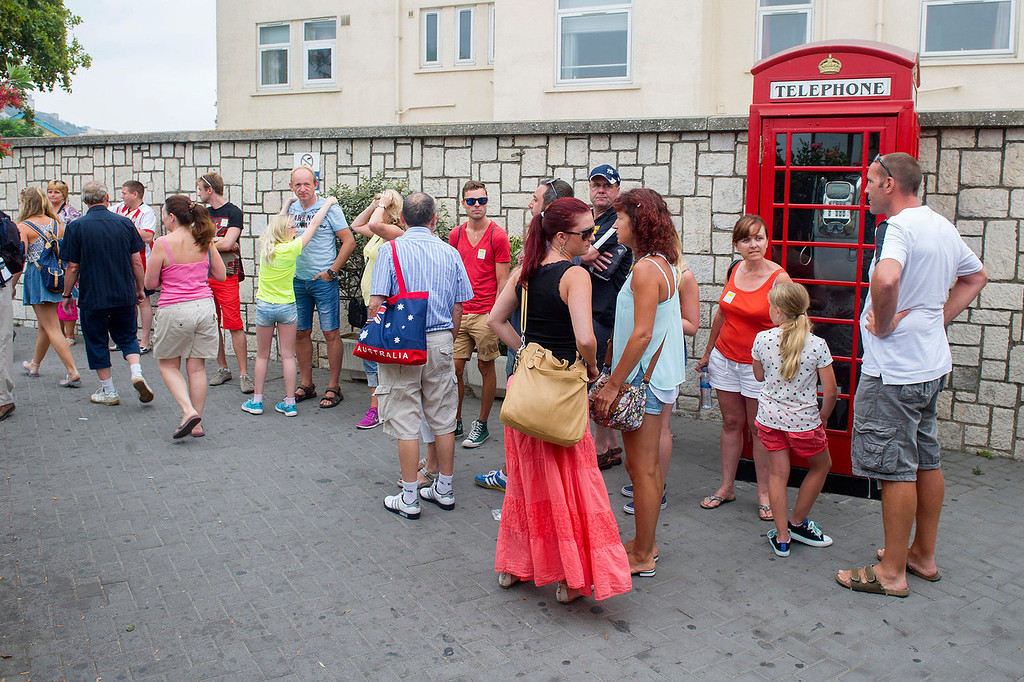. Tourists wait for taxis near a phone booth in Gibraltar on August 13, 2013. This rock of seven square kilometers enclosed in the coast of Andalusia, off the tip of southern Spain, is reminiscent of England: the red phone booths, mailboxes Royal Mail, the lampposts decorated with flowers, and double decker buses.   MARCOS MORENO/AFP/Getty Images