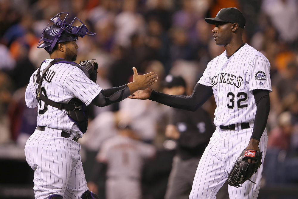 . Catcher Wilin Rosario #20 and relief pitcher LaTroy Hawkins #32 of the Colorado Rockies celebrate their victory over the San Francisco Giants at Coors Field on April 22, 2014 in Denver, Colorado. Hawkins earned a save as the Rockies defeated the Giants 2-1.  (Photo by Doug Pensinger/Getty Images)