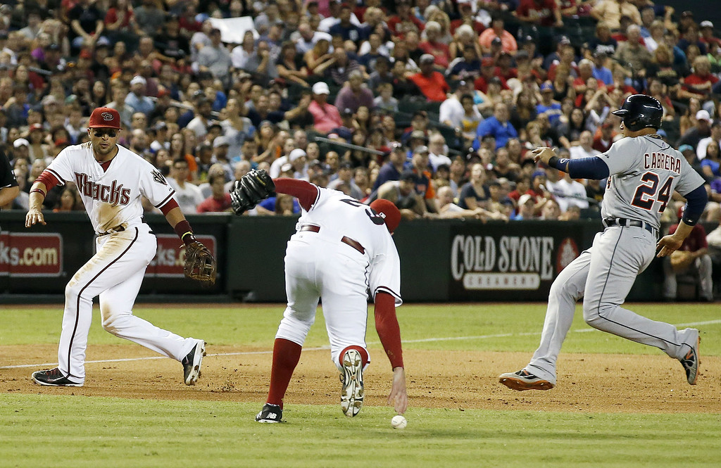 . Arizona Diamondbacks\' Brad Ziegler, middle, is unable to make a play on a ball that was hit off his chest by Detroit Tigers\' J.D. Martinez as Diamondbacks\' Martin Prado, left, looks on and Detroit Tigers\' Miguel Cabrera (24) starts his slide into third base during the eighth inning of a baseball game on Tuesday, July 22, 2014, in Phoenix. (AP Photo)