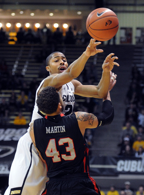 . Spencer Dinwiddie of Colorado gets a pass over Cedric Martin of Utah during the first half of the February 21st, 2013 game in Boulder. For more photos of the game, go to www.dailycamera.com. Cliff Grassmick / February 21, 2013