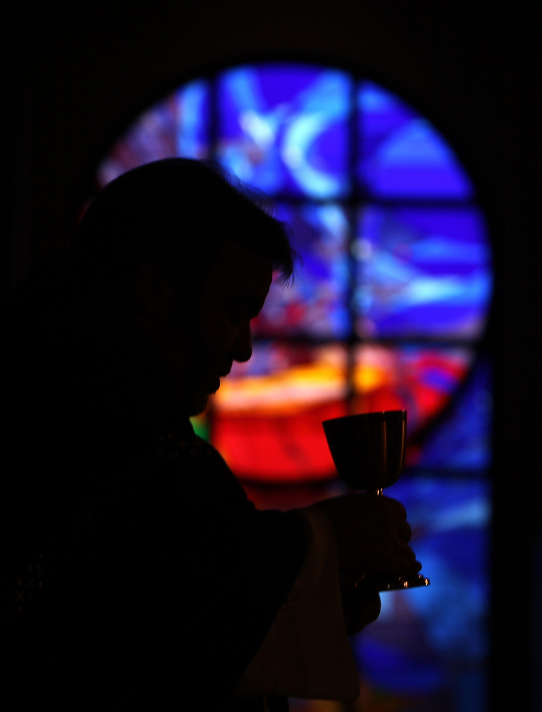 . Rev. Tom Rafferty leads communion during an Ash Wednesday service at St. Anthony of Padua Catholic Church in The Woodlands, Texas, Wednesday, March 5, 2014.  Ash Wednesday marks the beginning of the Lenten season, a time when Christians commit to acts of penitence and prayer in preparation for Easter Sunday.  (AP Photo/ The Courier, Jason Fochtman)