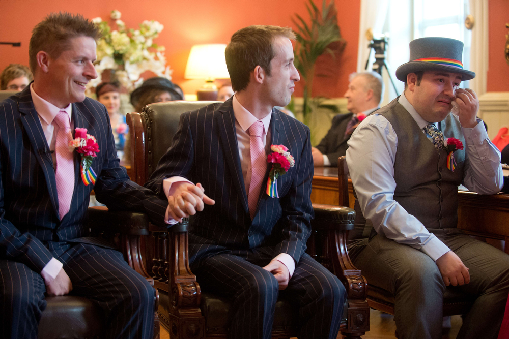 """. Phil Robathan (L) and James Preston (C) hold hands as a guest (R) reacts during their wedding ceremony in Brighton, southern England, on March 29, 2014. Gay couples across England and Wales said \""""I do\"""" as a law legalizing same-sex marriage came into effect at midnight, the final stage in a long fight for equality.  (LEON NEAL/AFP/Getty Images)"""