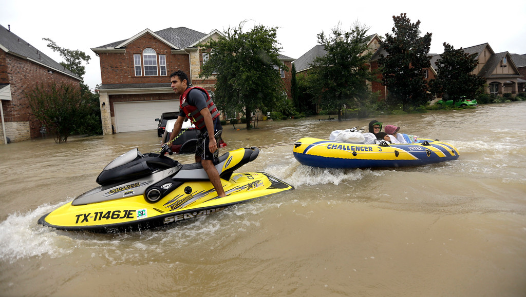 . Flood victims are towed to safety by a jet ski as floodwaters from Tropical Storm Harvey rise Monday, Aug. 28, 2017, in Spring, Texas. (AP Photo/David J. Phillip)
