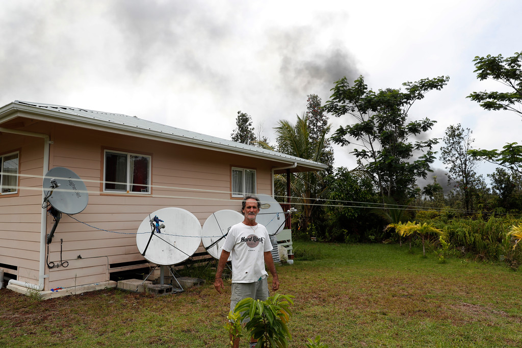 . With smoke from the lava flow in the background, Leilani Estates resident Sam Knox stands in the backyard of his home, Saturday, May 5, 2018, in Pahoa, Hawaii. Knox\'s home is less than a few 100 yards from the lava flow and he does not have any plans to evacuate. Knox is hopeful the lava will not take his home. (AP Photo/Marco Garcia)