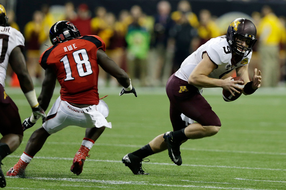 . Phillip Nelson #9 of Minnesota looks to pass as he is pressured by Micah Awe #18 of Texas Tech during the Meineke Car Care of Texas Bowl at Reliant Stadium on December 28, 2012 in Houston, Texas.  (Photo by Scott Halleran/Getty Images)