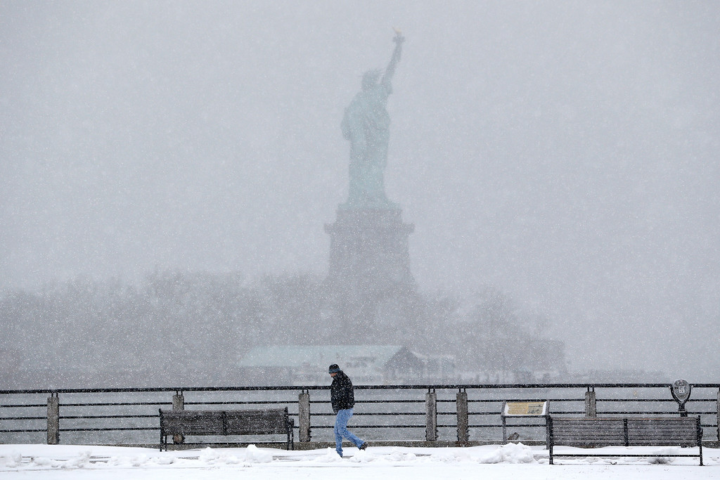 . A man strolls on a walking path at Liberty State Park, with the Statue of Liberty in the distance, Monday, Jan. 26, 2015, in Jersey City, N.J.  (AP Photo/Julio Cortez)