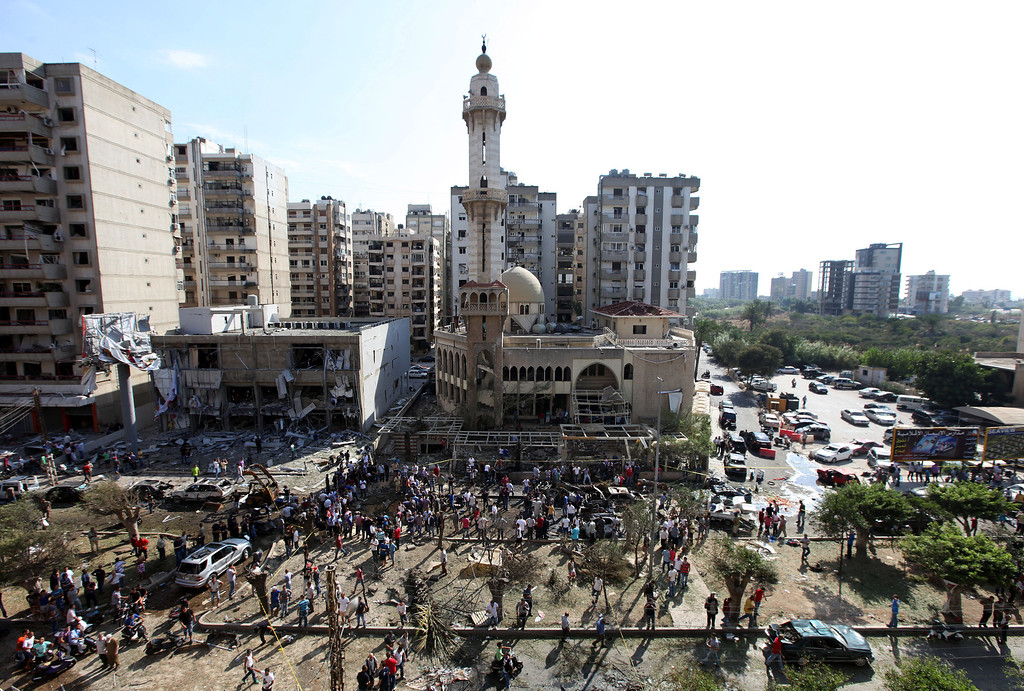 . People gather outside the Salam Mosque amid charred cars and wide damage, in the northern city of Tripoli, Lebanon, Friday Aug. 23, 2013. (AP Photo/Bilal Hussein)