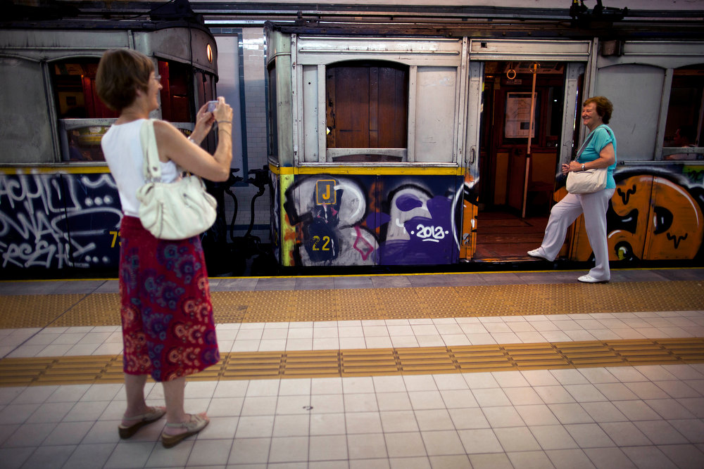 Description of . A woman poses for a picture in front of a wooden carriage car on the historic subway system in Buenos Aires, Argentina, Friday, Jan. 11, 2013.  The almost 100-year-old 'La Brugeoise