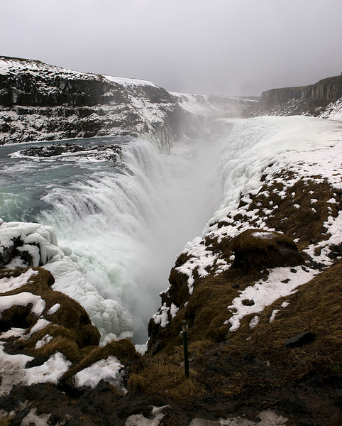 """Gullfoss (Golden Falls) is a massive waterfall located in the canyon of Hvítá river in southwest Iceland.  It is is one of the most popular tourist attractions in the country. The wide Hvítá rushes southward and 1km above the falls it turns sharply to the left and flows down into a wide curved three-step """"staircase"""" and then abruptly plunges in two stages into a crevice 105 ft deep. The crevice is 60 ft wide, and 2.5 km in length, is at right angles to the flow of the river.   The part frozen falls took my breath away as I first approached. Spectacular is just not grand enough to describe it. I trust the pictures help. More great close ups of the crevice. Olympus E3, 12-60mm SWD."""