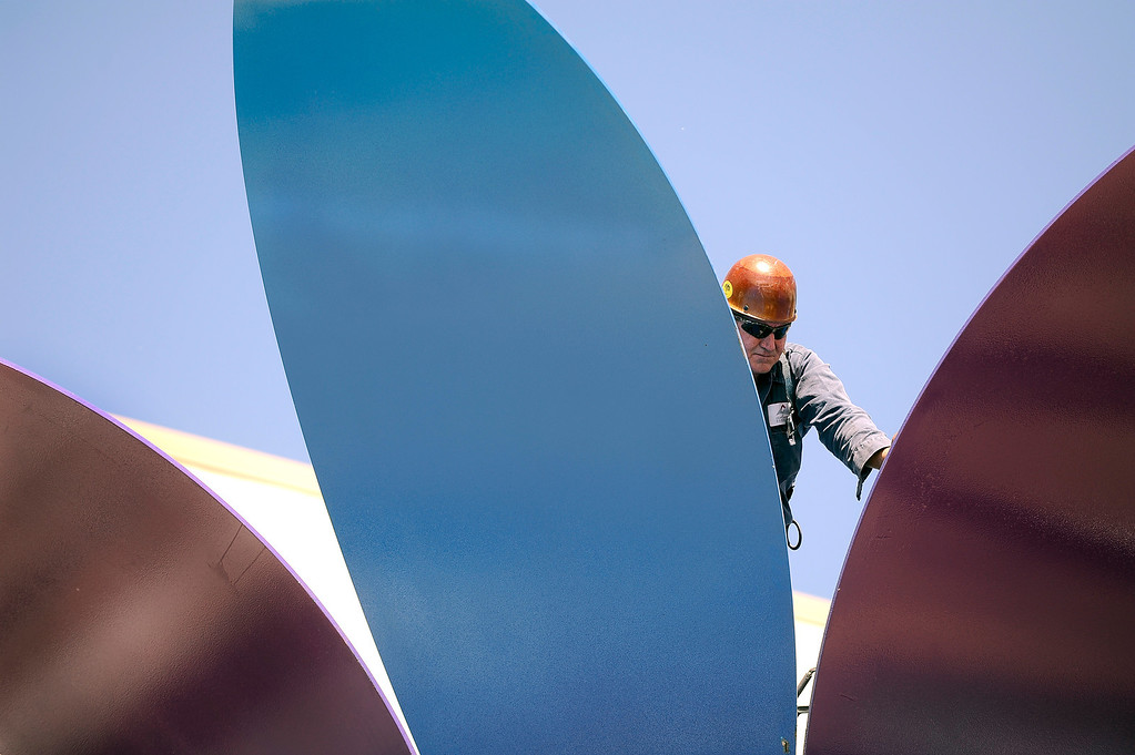 . Iron worker Brad Weaver,  from Peak Custom Fabrication, prepares a 30 foot-tall, 10-ton metal sculpture of a large flower titled Flor De La Alma by Denver artist Emanuel Martinez, so it can be topped off with a large white bulb that serves as the center of the flower. June 25, 2013.  (Photo By Kathryn Scott Osler/The Denver Post)