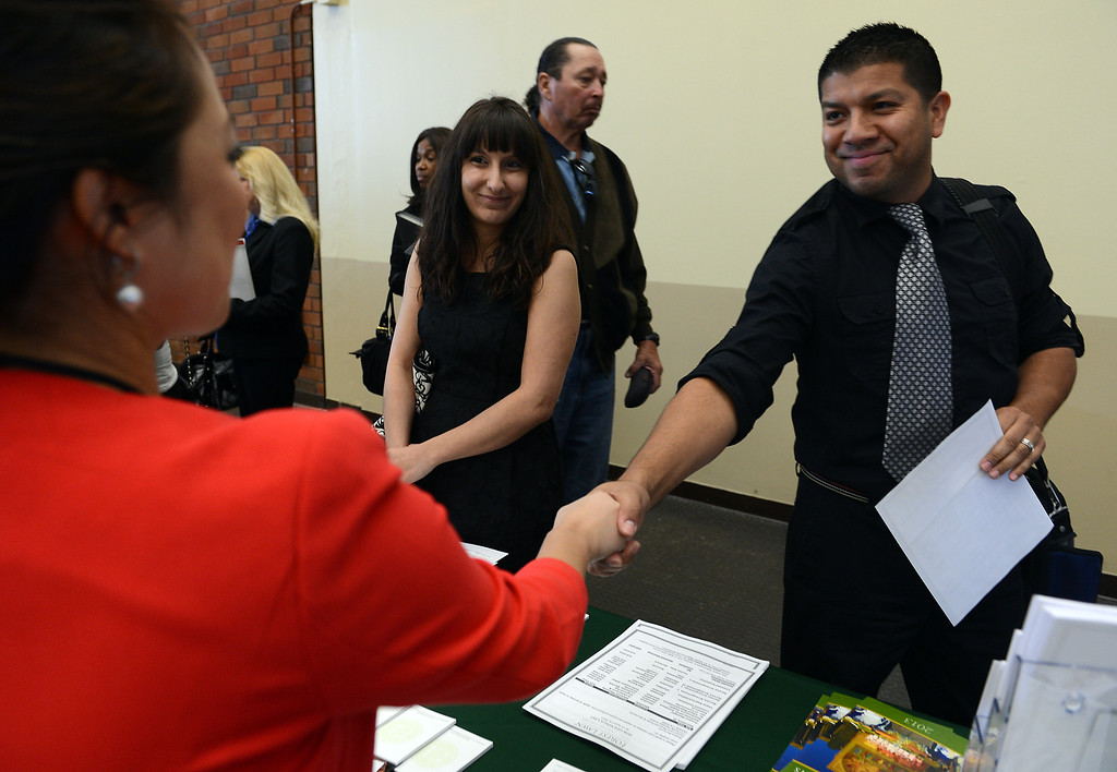 . Edward Ornelas, of Fontana, right, shakes hands with Laura Regoso, from Forest Lawn, during the San Bernardino County Workforce Investment Board\'s West End Spring Job Fair Wednesday, April 17, 2013, at LA/Ontario International Airport in Ontario. Jennifer Cappuccio Maher/Staff Photographer
