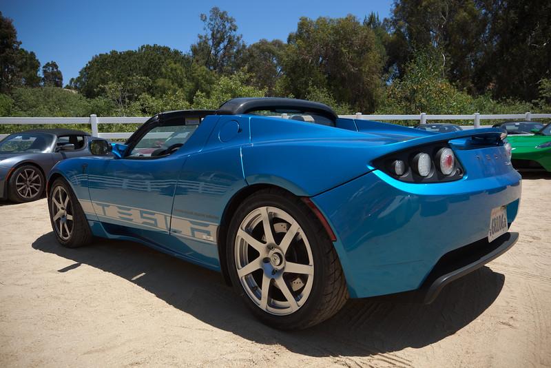 A blue Tesla under a very blue sky