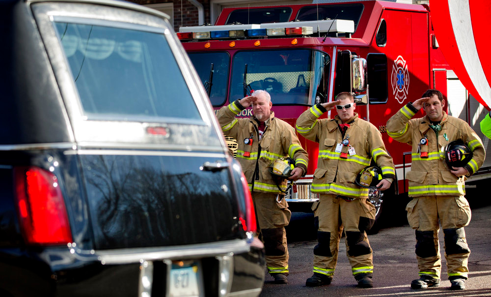 Description of . Firefighters salute as a hearse passes for the funeral procession to the burial of 7-year-old Sandy Hook Elementary School shooting victim Daniel Gerard Barden, Wednesday, Dec. 19, 2012, in Newtown, Conn. Barden was killed when Adam Lanza walked into Sandy Hook Elementary School in Newtown, Conn., Dec. 14, and opened fire, killing 26 people, including 20 children, before killing himself. (AP Photo/David Goldman)