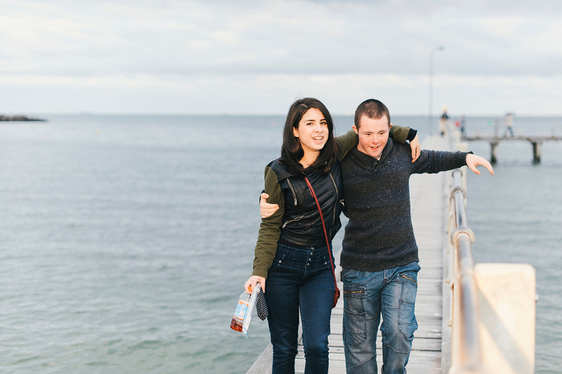 Teen with Down Syndrome and Young Woman Walking on a Jetty