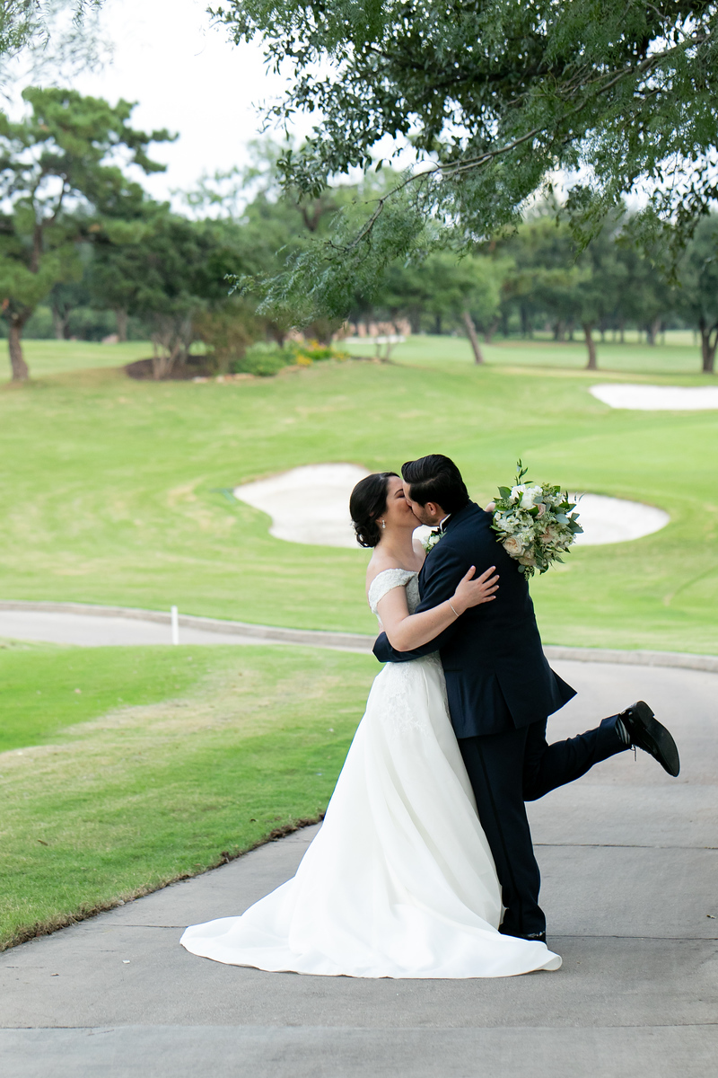 groom jokingly lifting his leg as he kisses his bride on a golf course