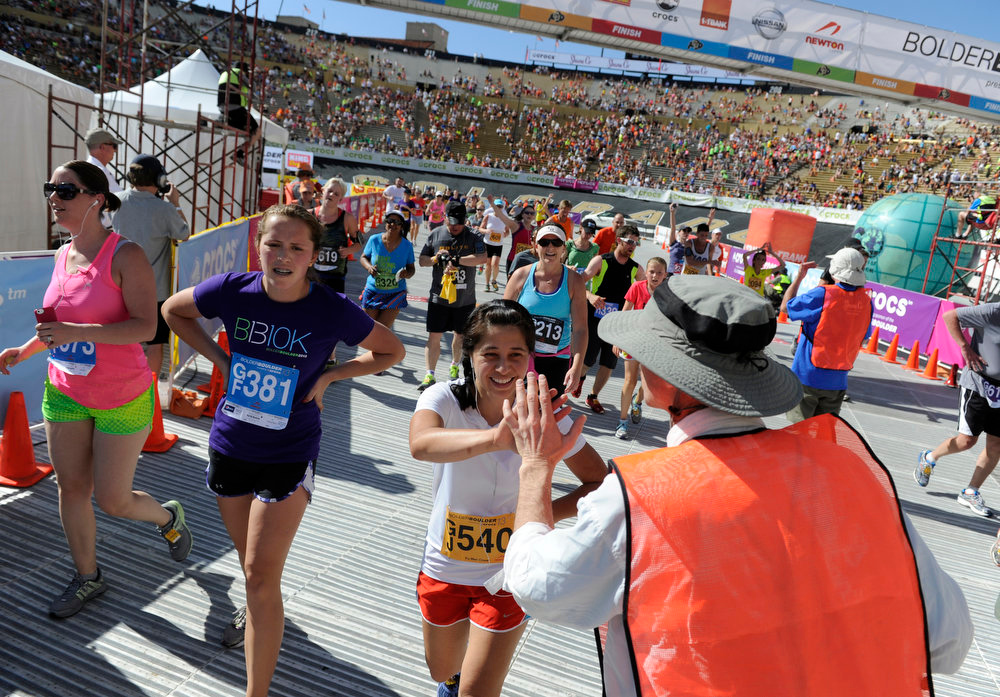 . Volunteer James Duncan gives runners a high-five after they cross the finish during the citizen\'s race. The 35th BolderBoulder 10k classic takes place on the streets of Boulder finishing at Folsom Field at the University of Colorado. (Photo By Kathryn Scott Osler/The Denver Post)