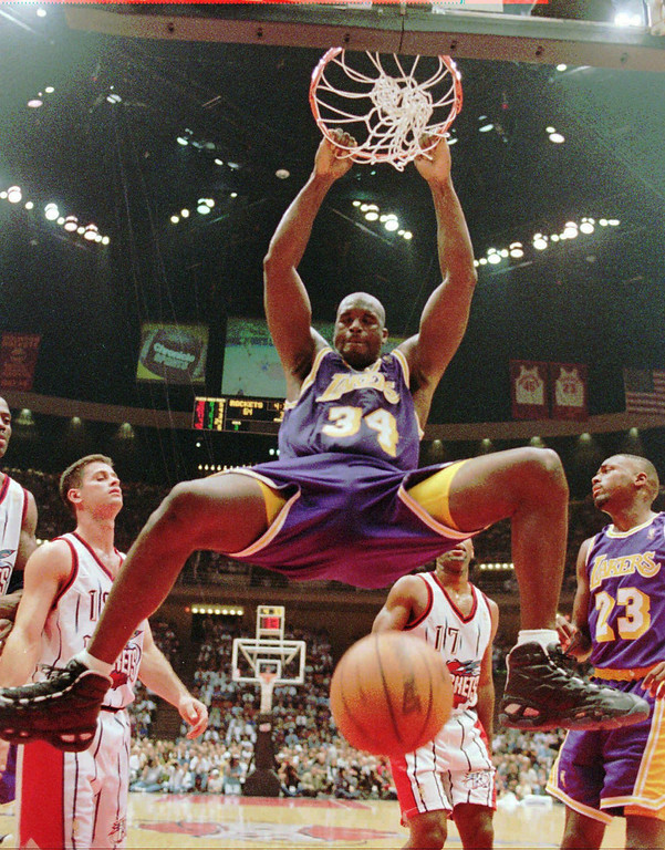 """. FILE - This Nov. 12, 1996, file photo shows Los Angeles Lakers\' Shaquille O\'Neal (34) hanging from the rim after a dunk during the third quarter against the Houston Rockets,  in Houston.  O\'Neal says on Twitter that he\'s \""""about to retire.\"""" (AP Photo/David J. Phillip, File)"""