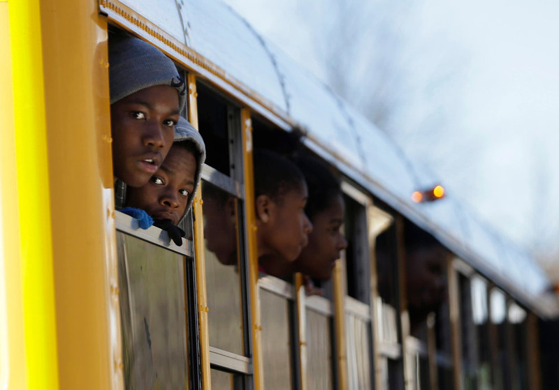 . Children look out from a school bus as they are transported to their parents after a shooting at an Price Middle school in Atlanta Thursday, Jan. 31, 2013. A 14-year-old boy was wounded outside the school Thursday afternoon and a fellow student was in custody as a suspect, authorities said. No other students were hurt. (AP Photo/John Bazemore)