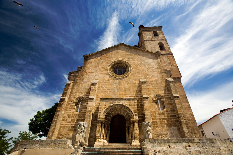 Storks flying over the Romanesque church of Santa Maria de Almocovar, built over a former mosque, Alcantara, Caceres, Spain