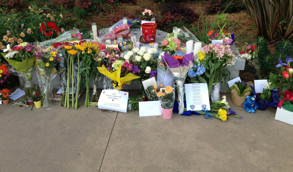 . Community residents are leaving flowers, cards and candles Wednesday outside Santa Cruz Police Station following the deaths of two detectives in the line of duty Tuesday. (Jessica M. Pasko/Sentinel)