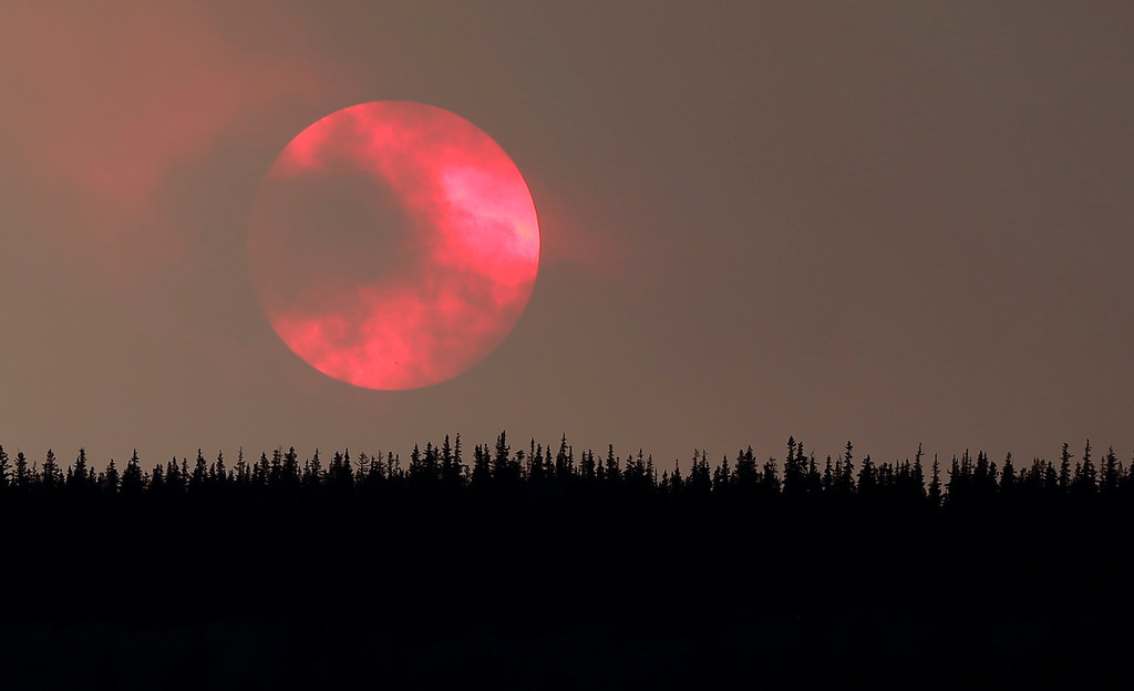 . Wildfire smoke masks the sun as it sets over a ridge Saturday, June 22, 2013, near South Fork, Colo.   (AP Photo/Gregory Bull)