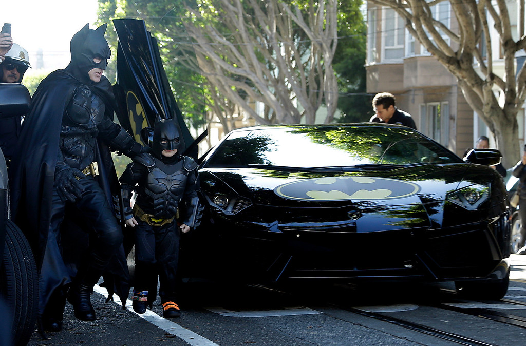 ". Miles Scott, dressed as Batkid, second from left, exits the Batmobile with Batman to save a damsel in distress in San Francisco, Friday, Nov. 15, 2013.  San Francisco turned into Gotham City on Friday, as city officials helped fulfill Scott\'s wish to be ""Batkid.\"" Scott, a leukemia patient from Tulelake in far Northern California, was called into service on Friday morning by San Francisco Police Chief Greg Suhr to help fight crime, The Greater Bay Area Make-A-Wish Foundation says. (AP Photo/Jeff Chiu)"