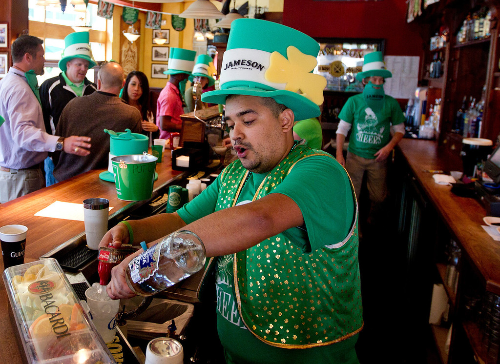 . Bartender Fez Galindo pours a drink for a patron on St. Patrick\'s Day at The Gooses Acre Bistro and Irish Pub, Monday, March 17, 2014, in The Woodlands, Texas. Employees handed out festive hats, beads, and fake beards while patrons were treated to live music and performances by Irish dancers. (AP Photo/Conroe Courier, Jason Fochtman)