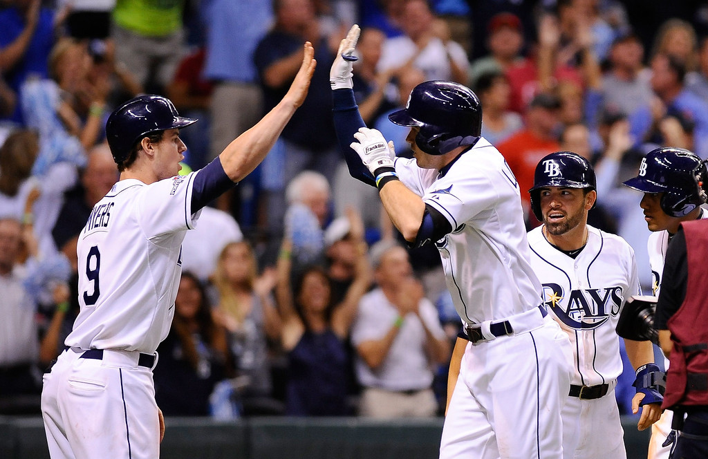 . Evan Longoria #3 of the Tampa Bay Rays celebrates with teammates after hitting a three-run home run in the fifth inning against the Boston Red Sox during Game Three of the American League Division Series at Tropicana Field on October 7, 2013 in St Petersburg, Florida.  (Photo by Brian Blanco/Getty Images)