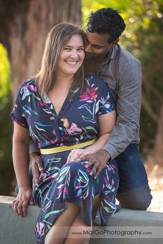 man in grey shirt kissing women in blue dress with pink flowers at Richmond Keller Beach
