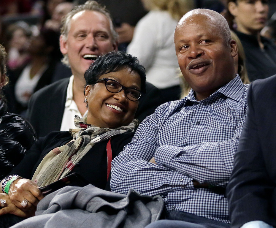 . Detroit Lions head coach Jim Caldwell, right, and wife Cheryl laugh at the antics of the Detroit Pistons mascot Hooper during the first half of an NBA basketball game against the Milwaukee Bucks, Friday, Nov. 7, 2014, in Auburn Hills, Mich. (AP Photo/Duane Burleson)