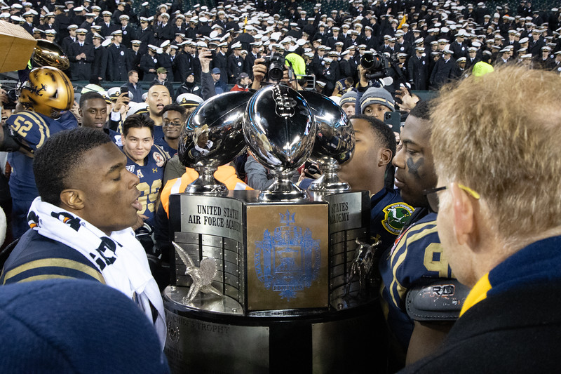 Navy players raise the Commander in Chief's Trophy after defeating Army.