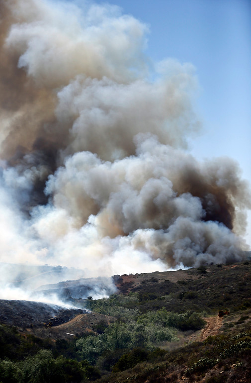 . Billowing smoke rises from flames as firefighters begin the trek up the hills to battle a wild fire, Tuesday, May 13, 2014, in San Diego.  (AP Photo)