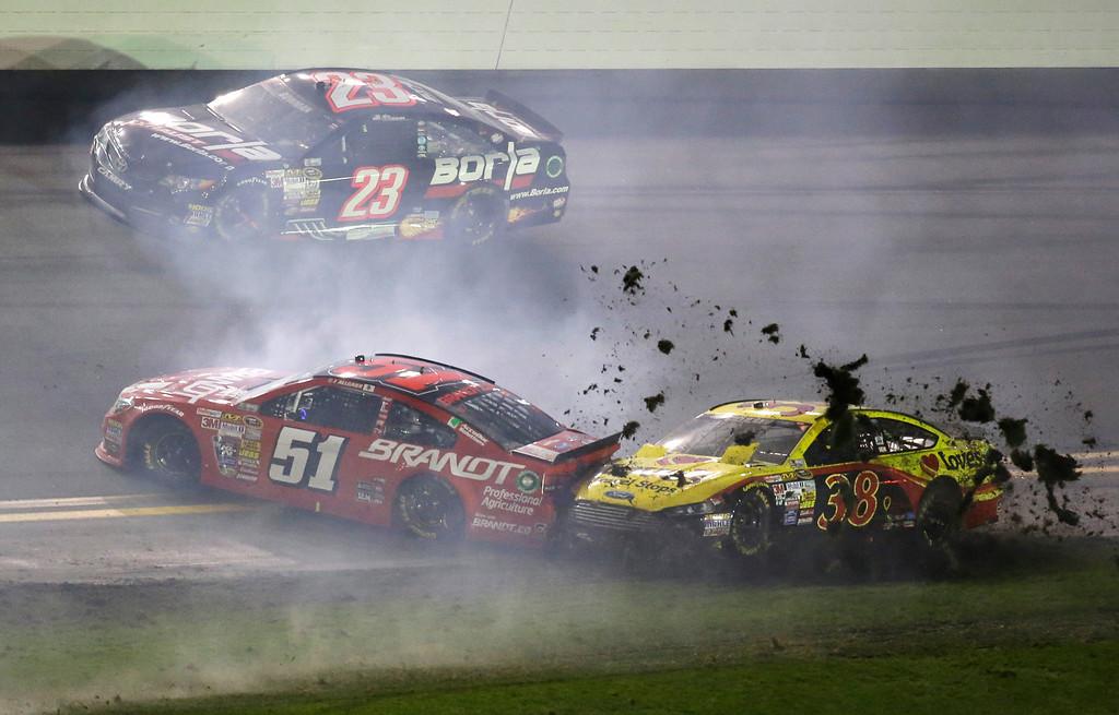 . Justin Allgaier (51) and David Gilliland (38) are involved in a crash as Alex Bowman (23) drives past during the NASCAR Daytona 500 Sprint Cup series auto race at Daytona International Speedway in Daytona Beach, Fla., Sunday, Feb. 23, 2014. (AP Photo/John Raoux)