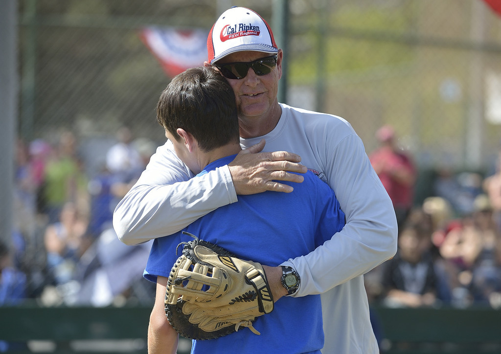 . LONG BEACH, CALIF. USA -- Los Altos Youth Baseball and Softball league president, Dwayne Fowler, hugs his oldest son, Andrew Fowler, after Andrew delivered one of three first pitches during opening ceremonies at El Dorado Park in Long Beach, Calif. on March 2, 2013. Fowler\'s other children, Jacob Fowler and Makayla Fowler delivered the other first pitches. Their mother, Colette Fowler, who was in charge of the snack bar and was a huge part of the league, died of cancer last September.  Photo by Jeff Gritchen / Los Angeles Newspaper Group
