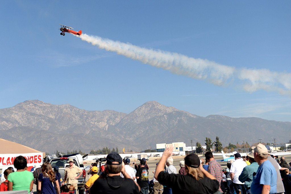. Spectators watch as an airplane performs aerobatics during the 39th annual Cable Airshow and Car Show at Cable Airport in Upland, Saturday, Jan. 11, 2014.(John Valenzuela/Staff Photographer)