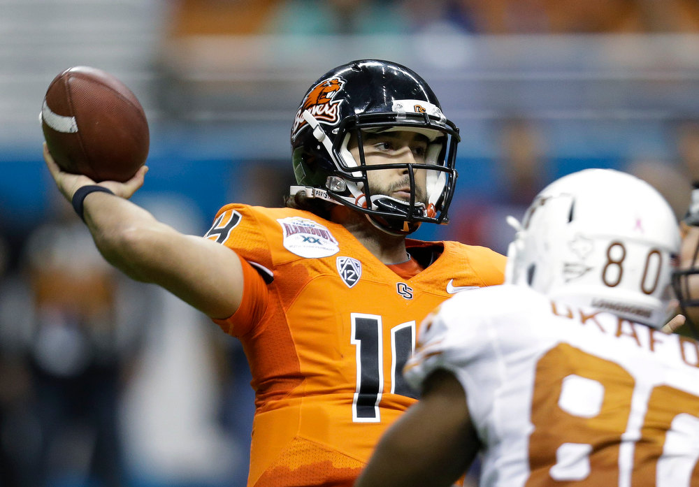 . Oregon State\'s Jordan Poyer, left, throws as Texas defender Alex Okafor (80) pressures him during the second quarter of the Alamo Bowl NCAA football game, Saturday, Dec. 29, 2012, in San Antonio.  (AP Photo/Eric Gay)
