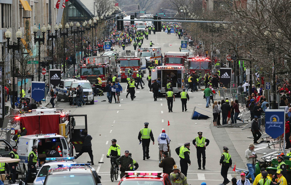 . Medical workers respond following an explosion at the 2013 Boston Marathon in Boston, Monday, April 15, 2013. Two explosions shattered the euphoria of the Boston Marathon finish line on Monday, sending authorities out on the course to carry off the injured while the stragglers were rerouted away from the smoking site of the blasts. (AP Photo/The Boston Globe, David L Ryan)