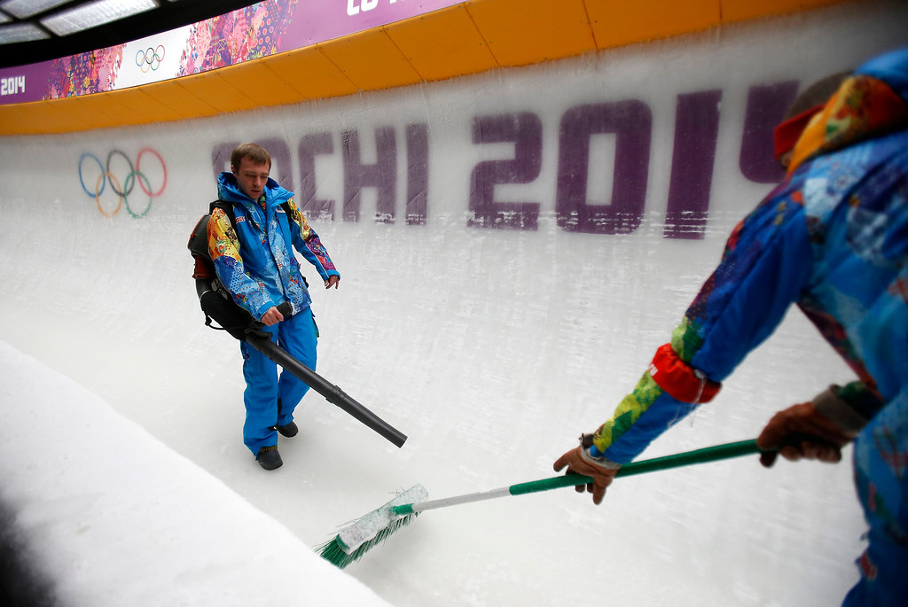 . Workers prepare the course for the Two-man Bobsleigh at the Sanki Sliding Center for the 2014 Winter Olympics in Krasnaya Polyana, Russia, on Sunday, Feb. 16, 2014.  (Nhat V. Meyer/Bay Area News Group)