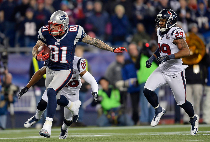 . New England Patriots tight end Aaron Hernandez (81) runs for a long gain deep into Houston Texans territory after catching a pass from quarterback Tom Brady during the third quarter of their NFL AFC Divisional playoff football game against the Houston Texans in Foxborough, Massachusetts January 13, 2013. At right is Texans\' Glover Quin and at back left is Texans\' Brandon Harris.  REUTERS/Gretchen Ertl