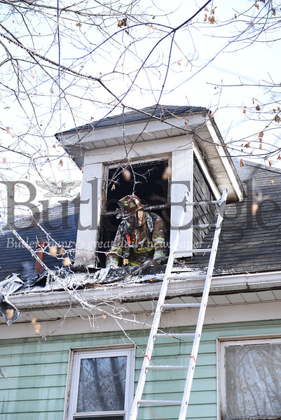 A firefighter called the scene of an attic fire at 112 South Street Thursday, December 12, 2019, sticks his head out of an attic window after spraying down the area and throwing out insulation.,Photo by Lauryn Halahurich/Butler Eagle,--